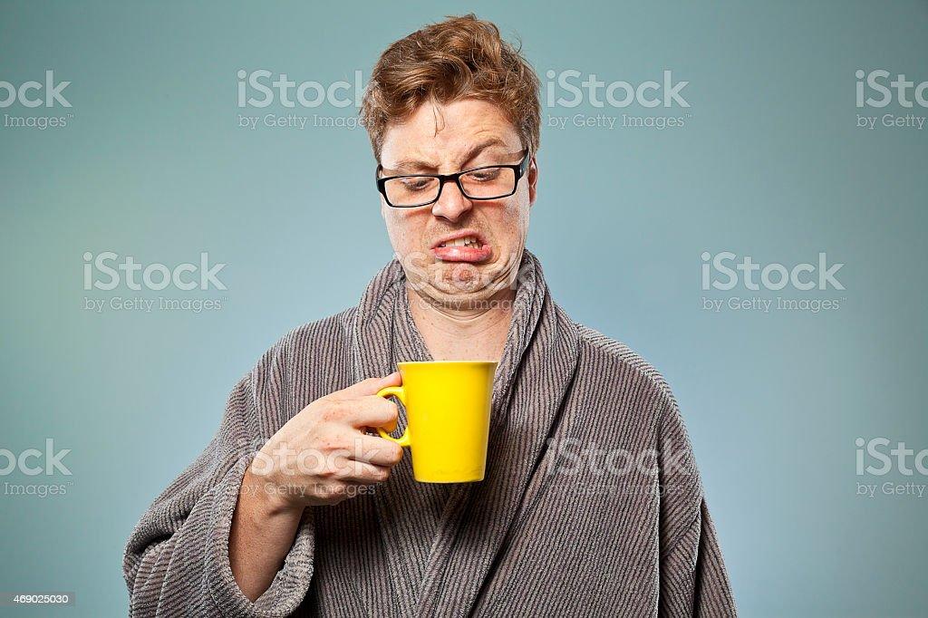 Nerdy guy drinking bad coffee stock photo
