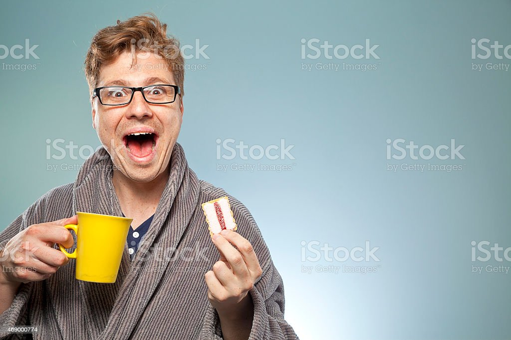 Nerdy guy smiling with a coffee and biscuit stock photo