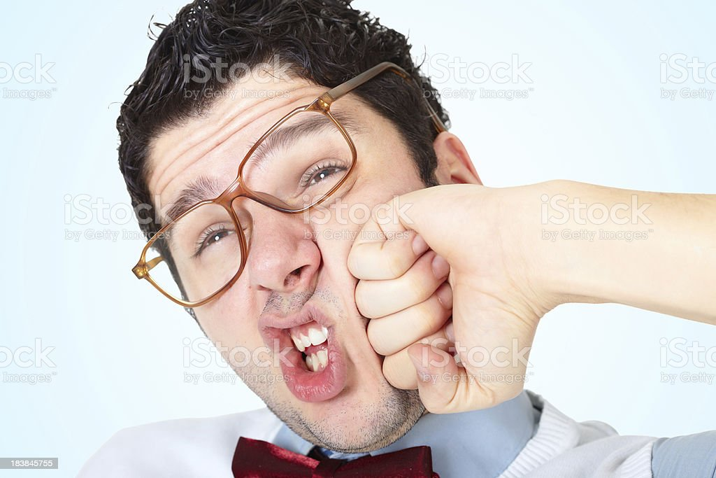 Nerdy guy wearing glasses receive a punch in face royalty-free stock photo