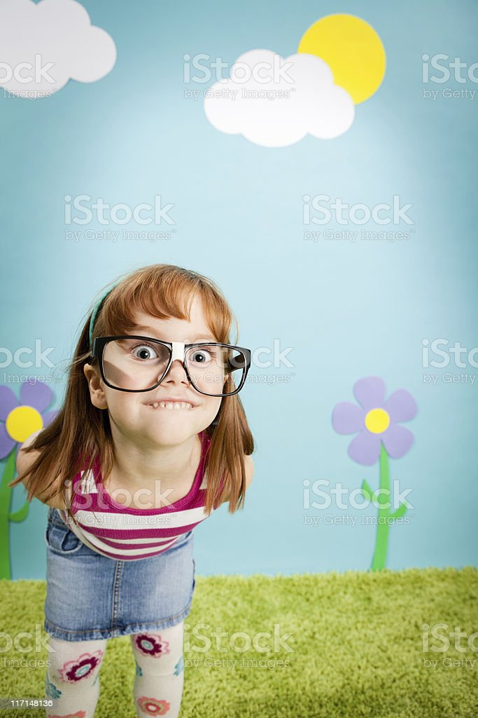 Nerdy Little Girl Smiling in Whimsical, Outdoor World royalty-free stock photo