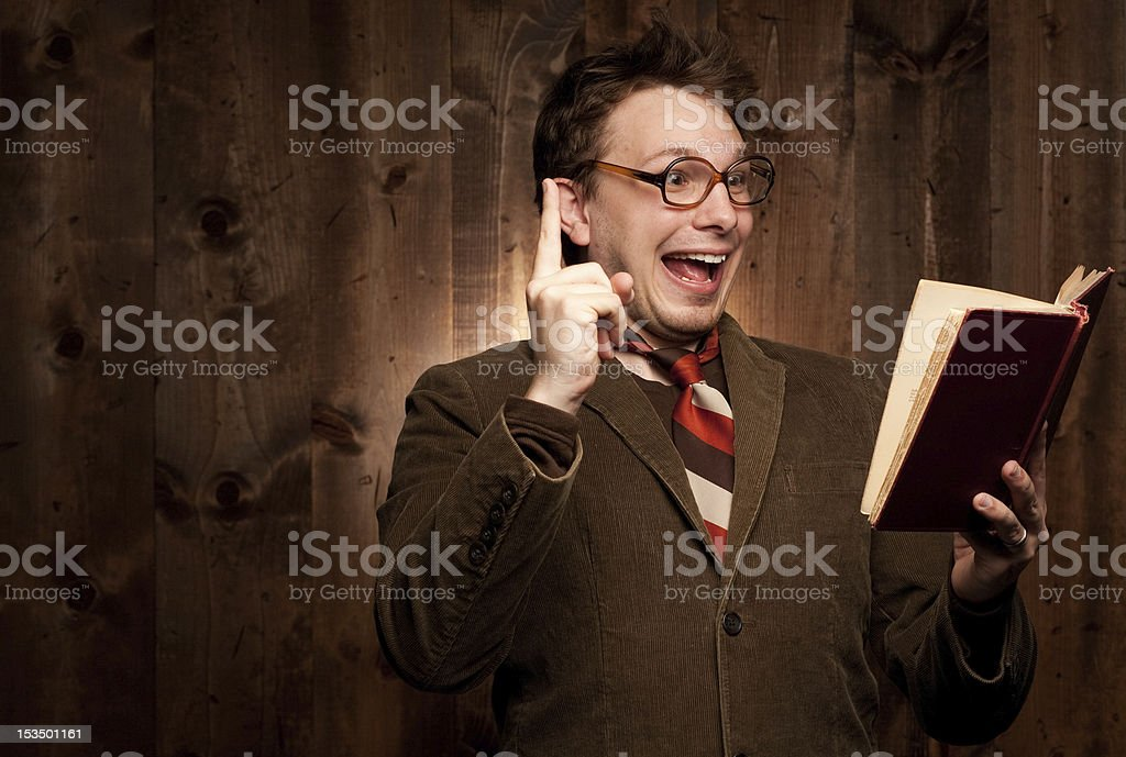 Nerdy man in brown with glasses and book having idea. royalty-free stock photo