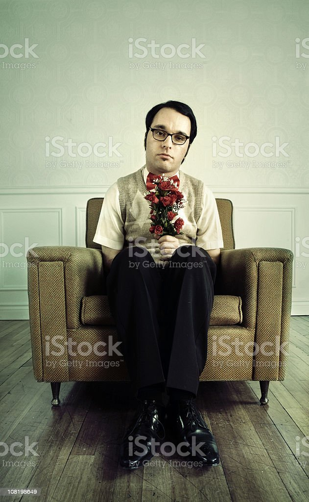 Nerdy Man Sitting in Chair with Flowers stock photo