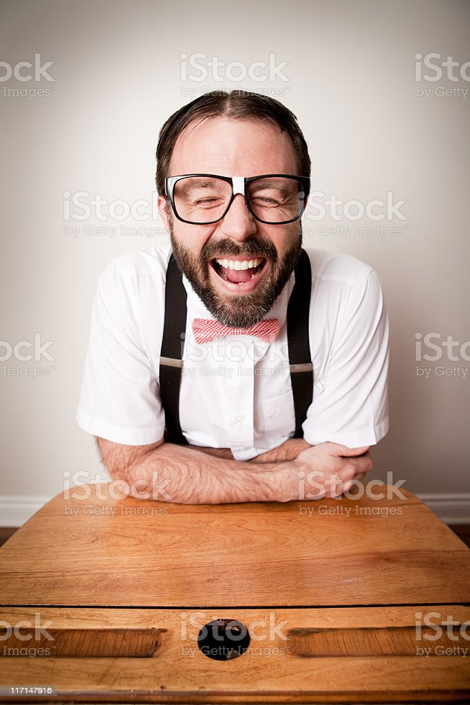 Nerdy Man Student Laughing while Sitting in School Desk stock photo