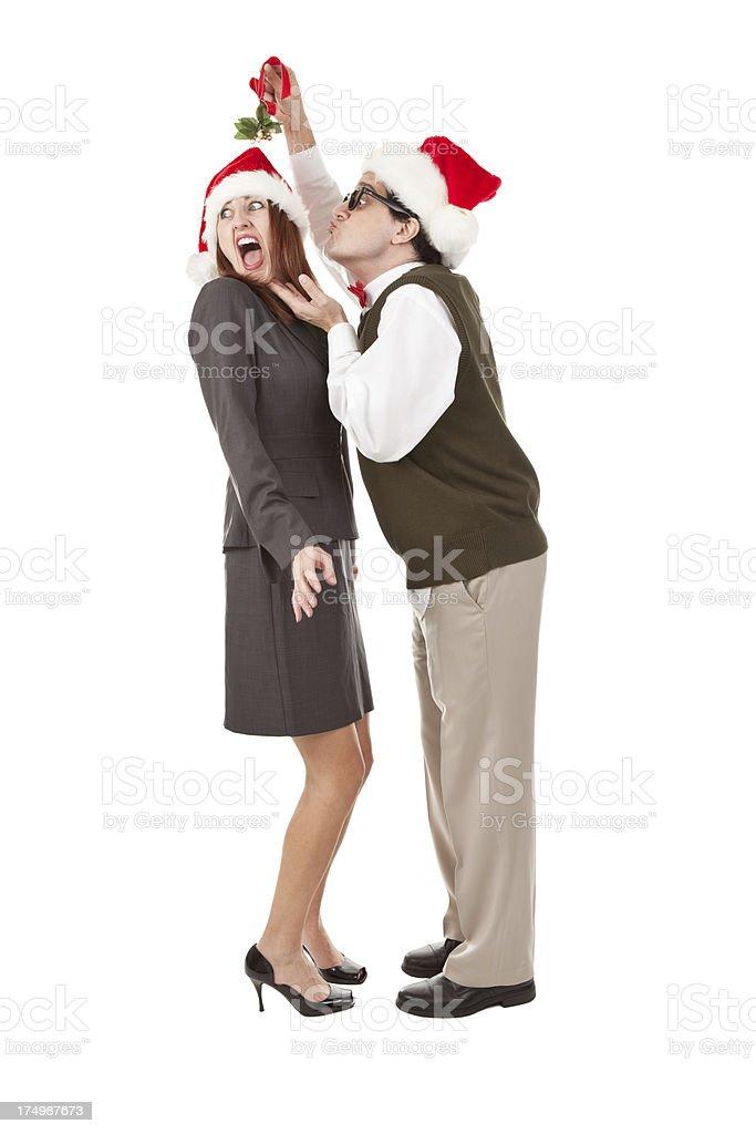 Nerdy Man Trying to Kiss Screaming Woman Under Mistletoe royalty-free stock photo