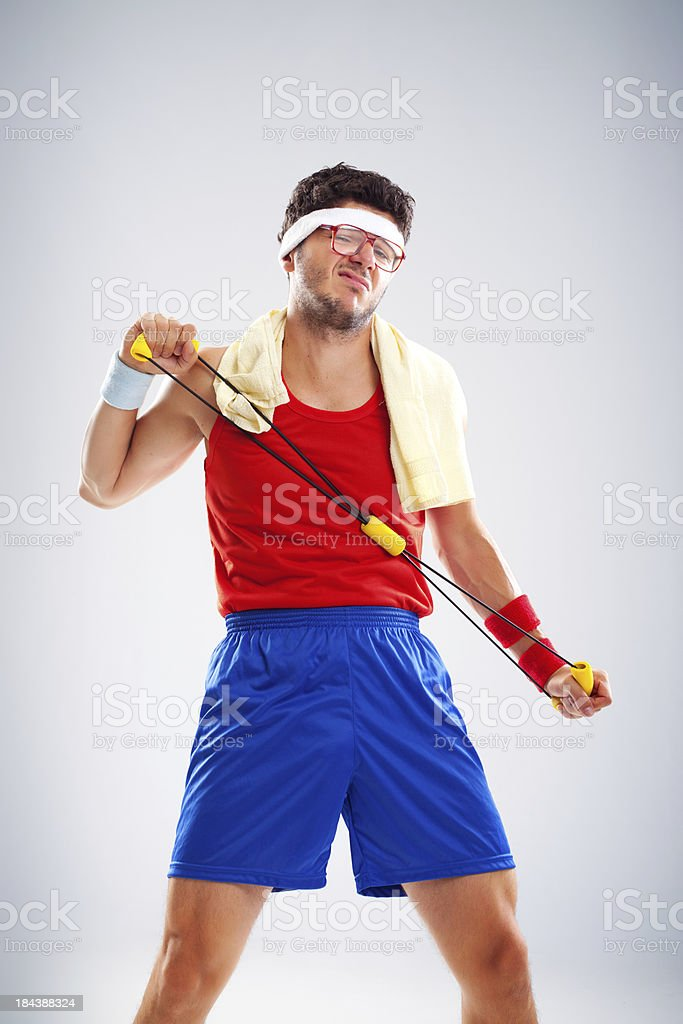Nerdy man with glasses exercising with chest expander stock photo