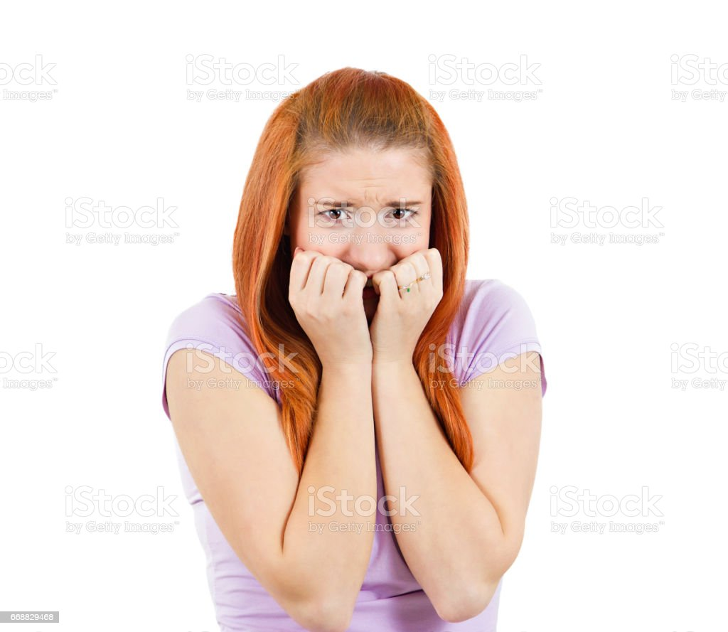 nerdy young, redhead woman biting her finger nails, looking at you with craving for something, stock photo
