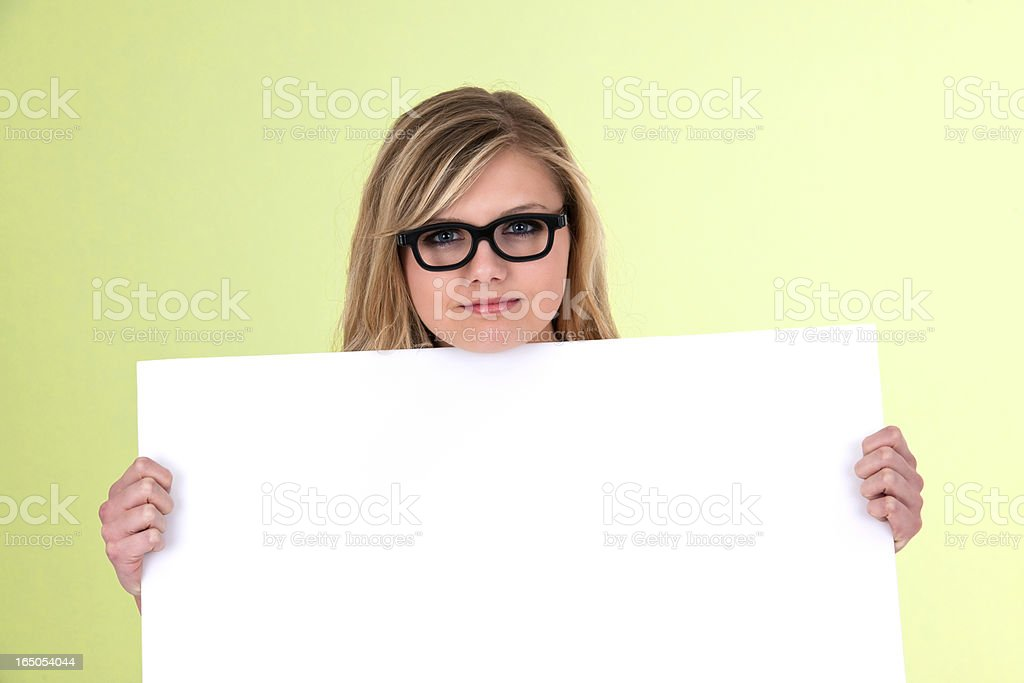 Nerdy Young Woman Holding Blank Placard royalty-free stock photo