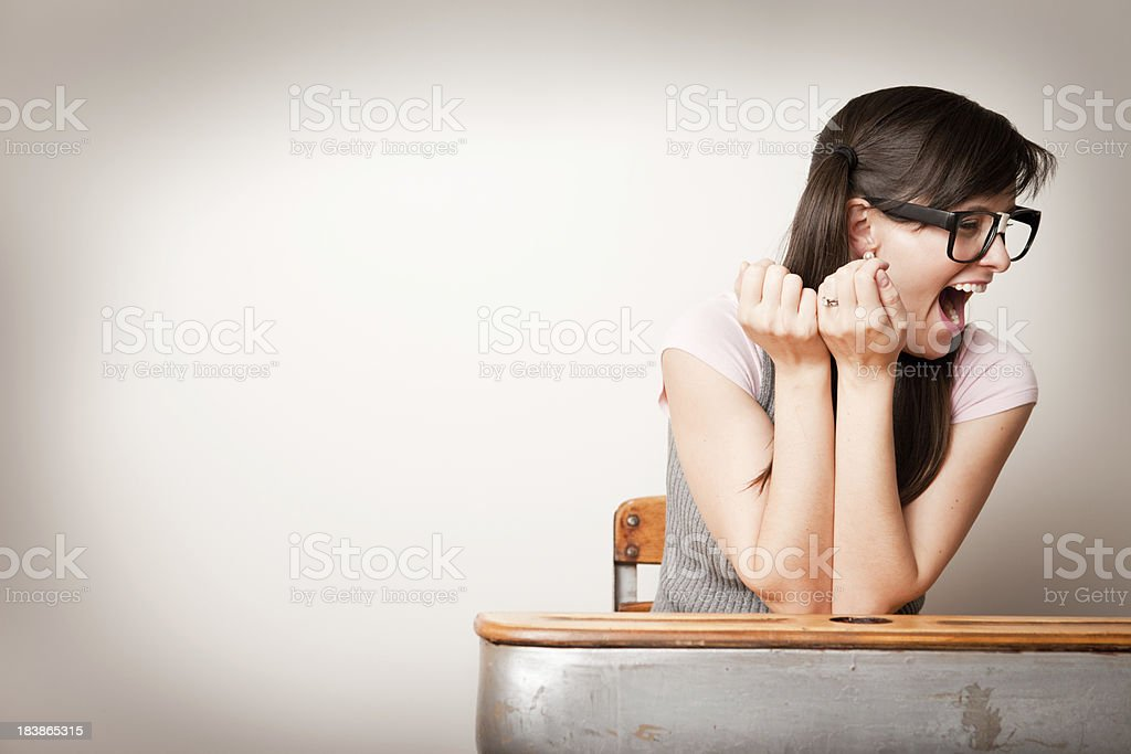 Nerdy Young Woman Student Laughing While Sitting  in School Desk royalty-free stock photo