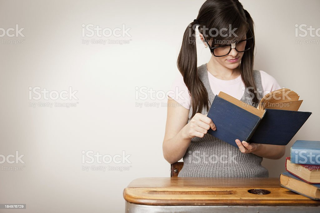 Nerdy Young Woman Student Sitting at School Desk Reading stock photo
