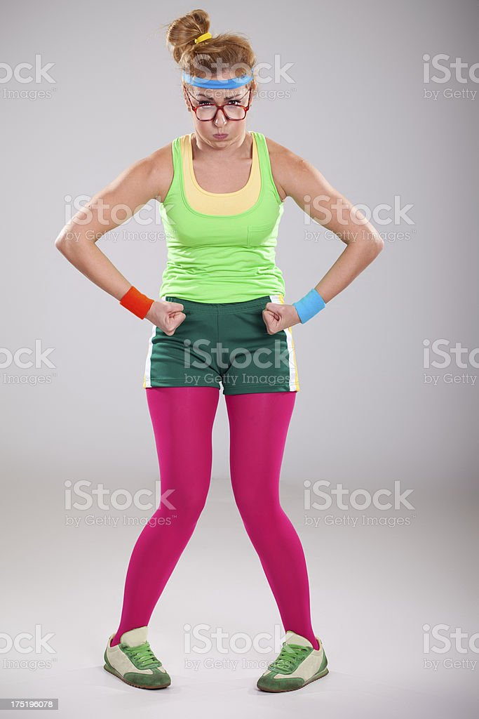 Nerdy young woman with glasses  showing her muscular body royalty-free stock photo