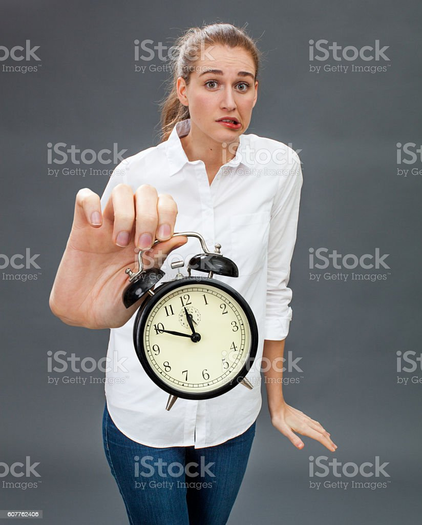 nervous beautiful girl showing an annoying alarm clock for deadlines stock photo