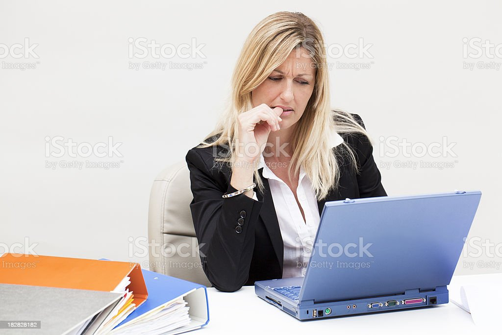 Nervous blond businesswoman sitting at laptop biting nail royalty-free stock photo