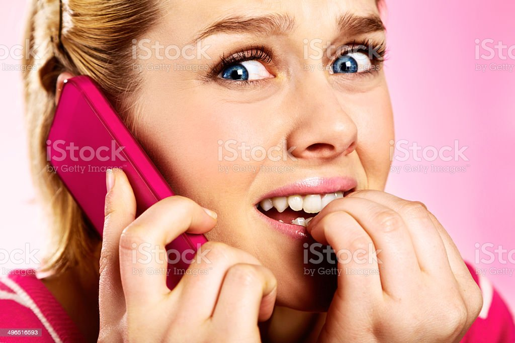 Nervous blonde teenager listening on cellphone bites nails fearfully stock photo