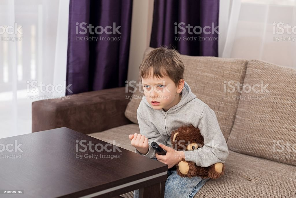 Nervous child sitting on the sofa and watching tv stock photo