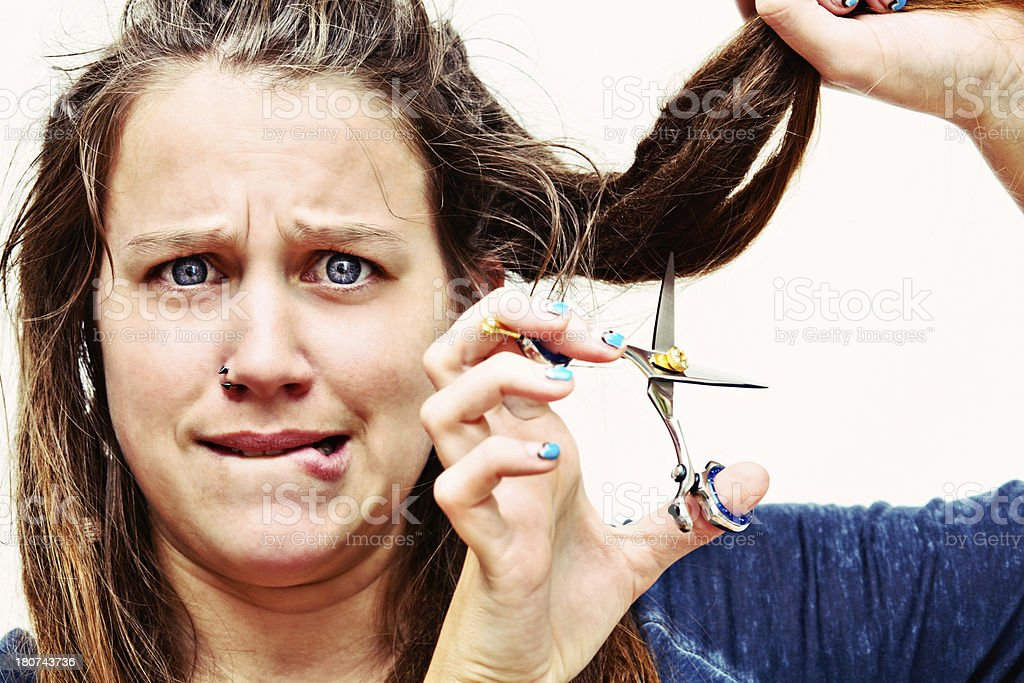 Nervous, dreadlocked brunette prepares to cut her hair royalty-free stock photo