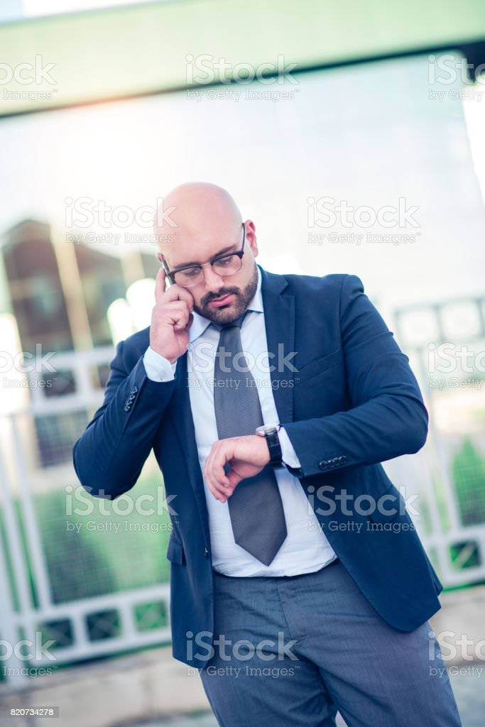 Nervous Late Businessman Talking On The Phone In Front of Office Building stock photo