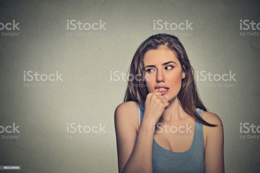 nervous looking young woman biting her fingernails stock photo
