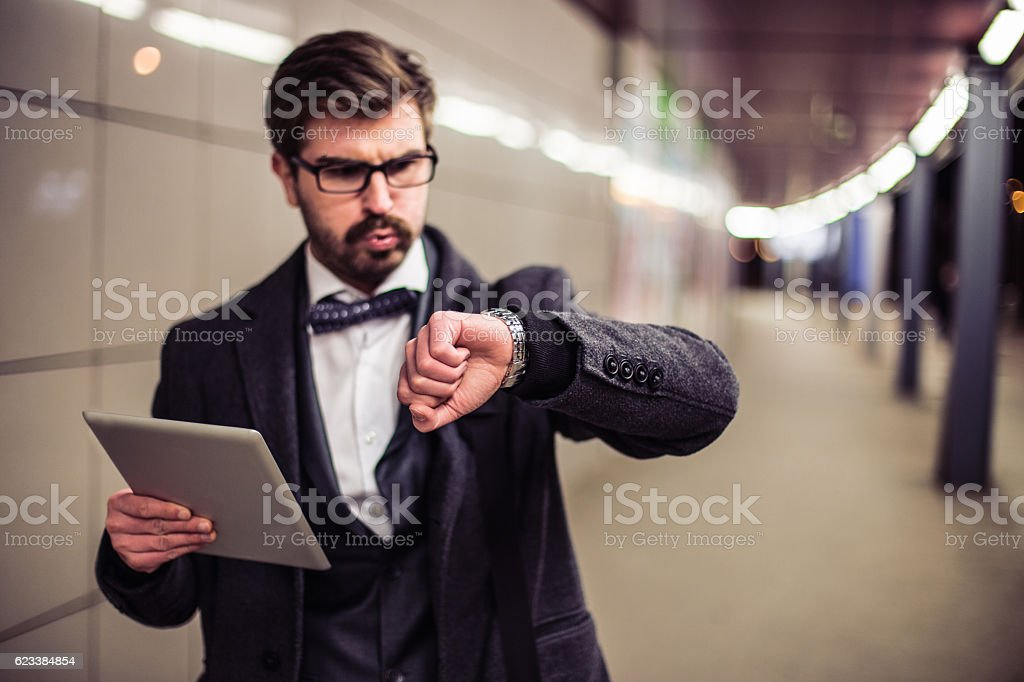 Nervous man being late and watching at hand clock stock photo