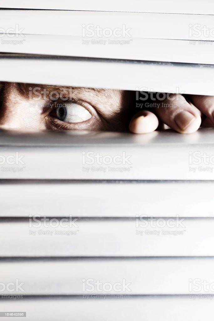 Nervous man looks sideways behind venetian blind royalty-free stock photo
