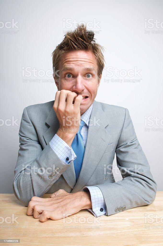 Nervous Office Worker Businessman Biting His Fingernails at Desk stock photo