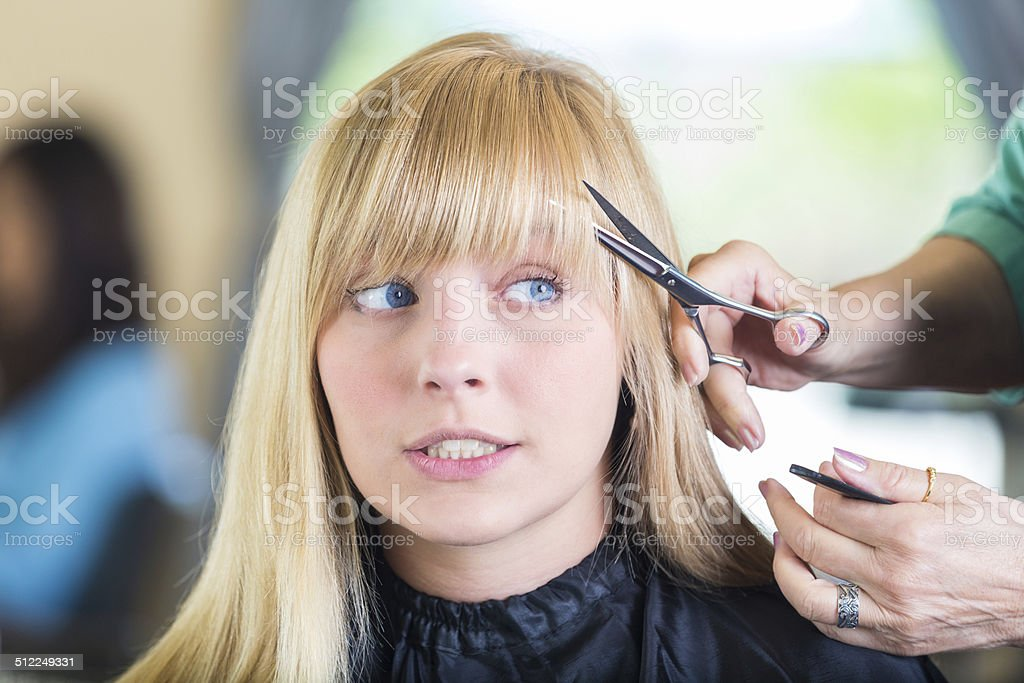 Nervous salon client having bangs trimmed during haircut appointment stock photo
