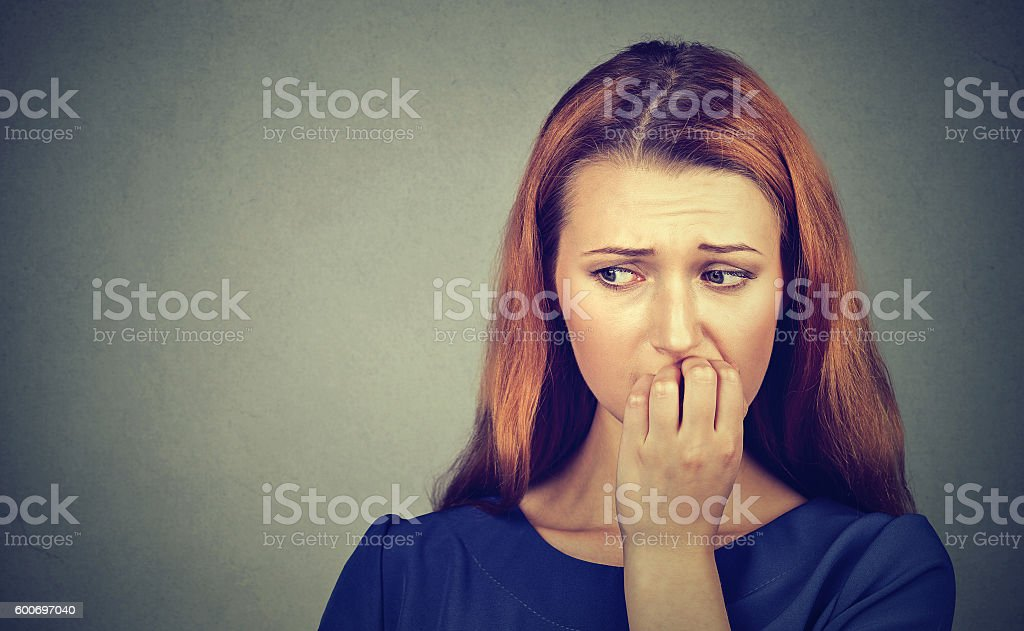 Nervous woman biting fingernails craving or anxious stock photo
