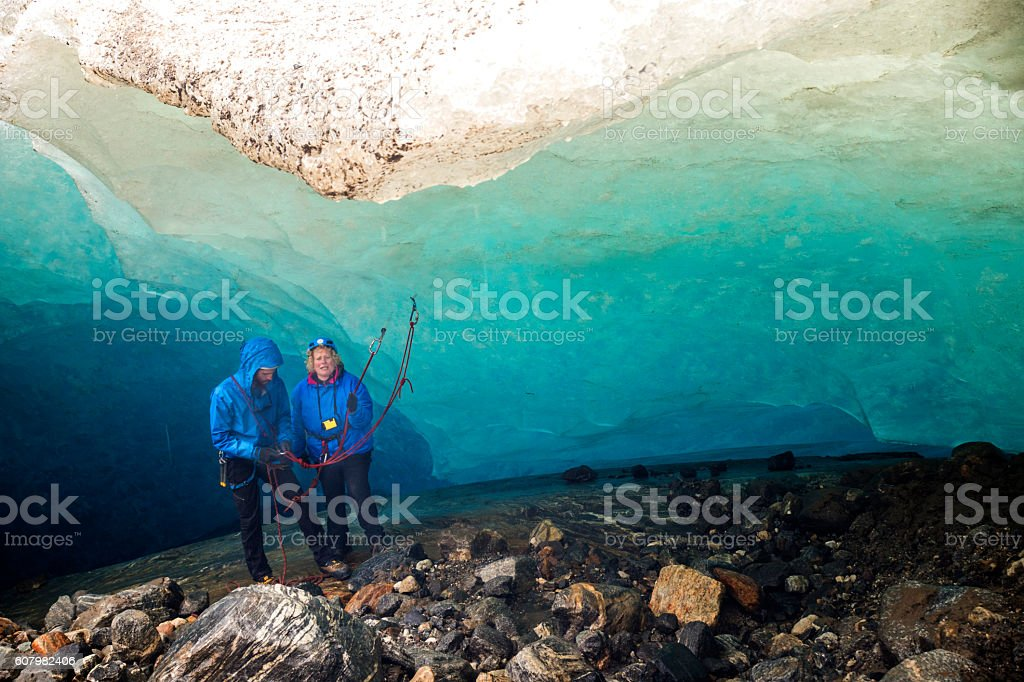 Nervous woman prepares to rappel in ice cave stock photo