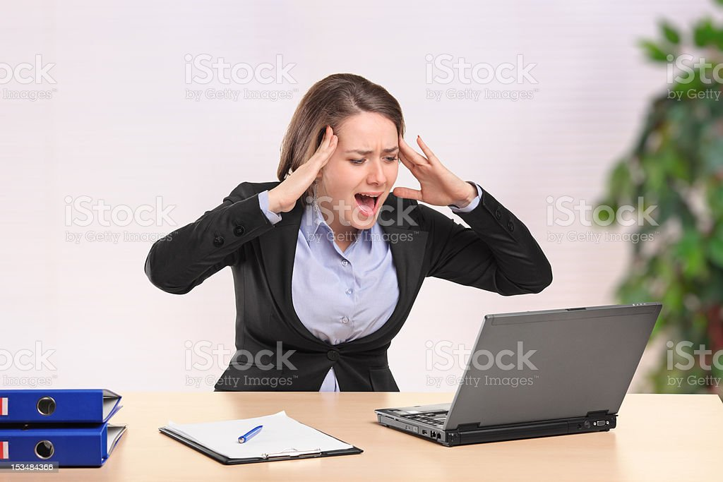 Nervous young businesswoman yelling to a laptop royalty-free stock photo