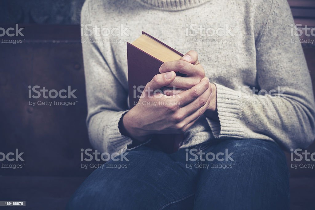 Nervous young man clutching book stock photo