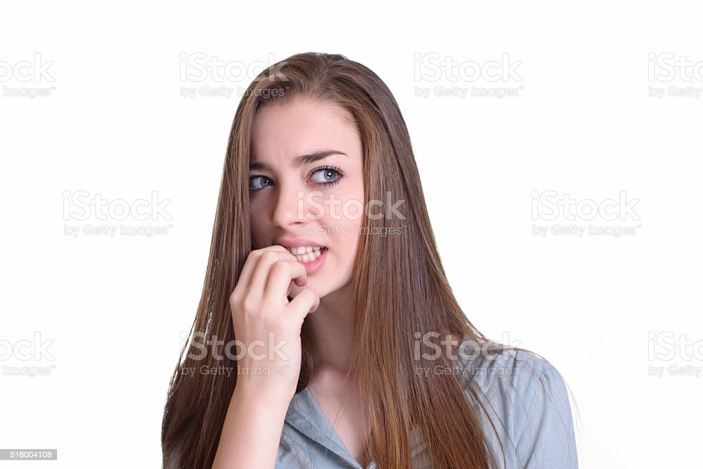 Nervous young woman biting her nails stock photo