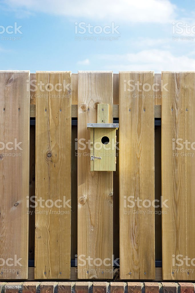 Nest box hanging on wooden fence royalty-free stock photo