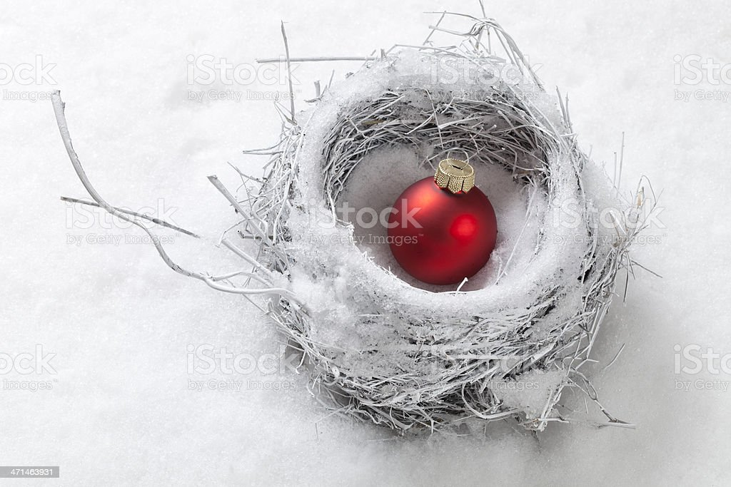 Nest in the snow with Christmas ball stock photo