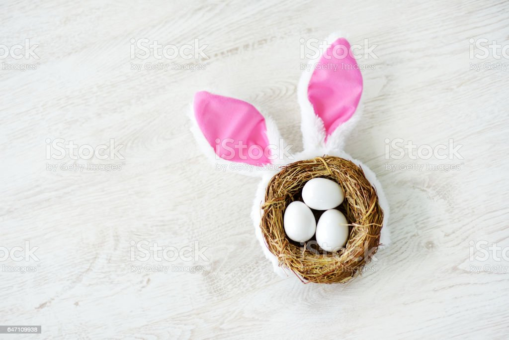 A nest with three white Easter eggs and bunny ears at home on Easter day stock photo