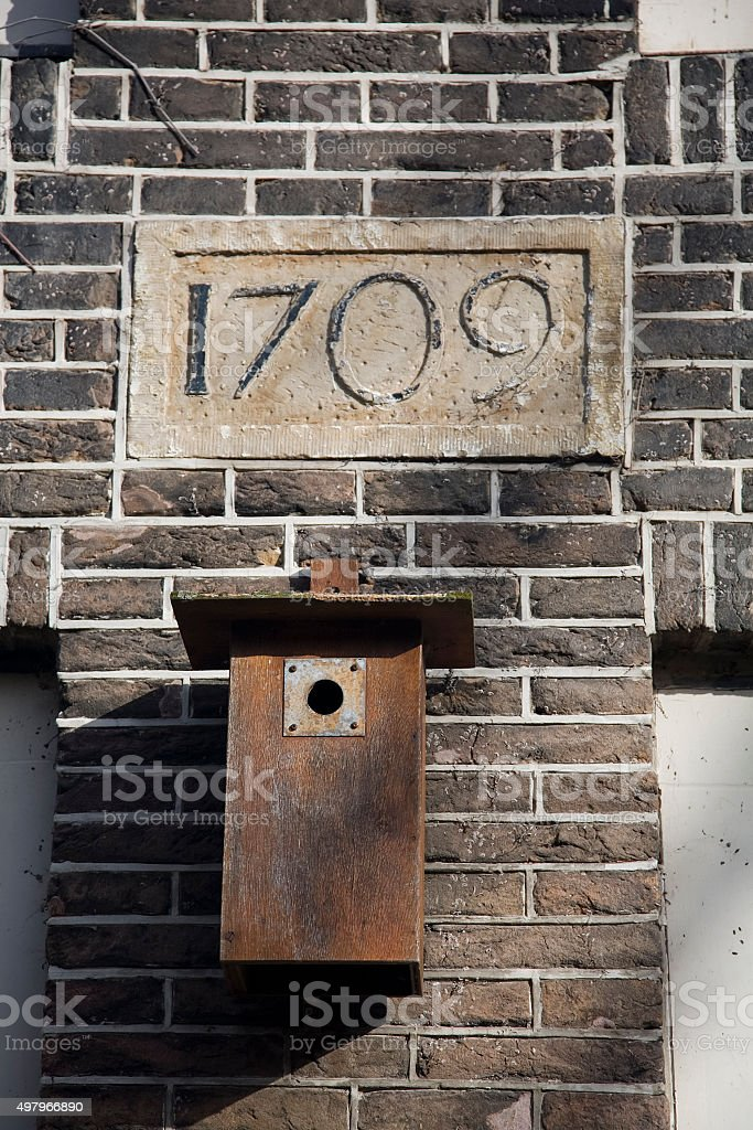 Nestbox against a wall with inscription 1709 stock photo