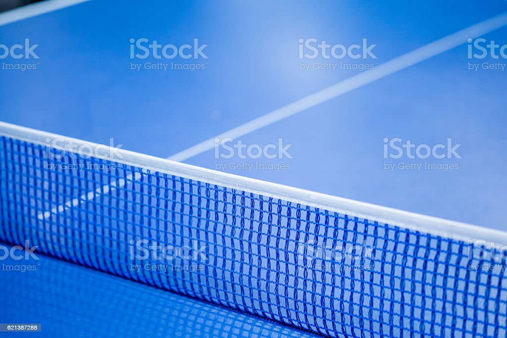 Net on blue ping pong table stock photo