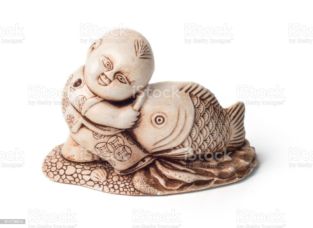 Netsuke of the boy with big fish. Isolated. stock photo