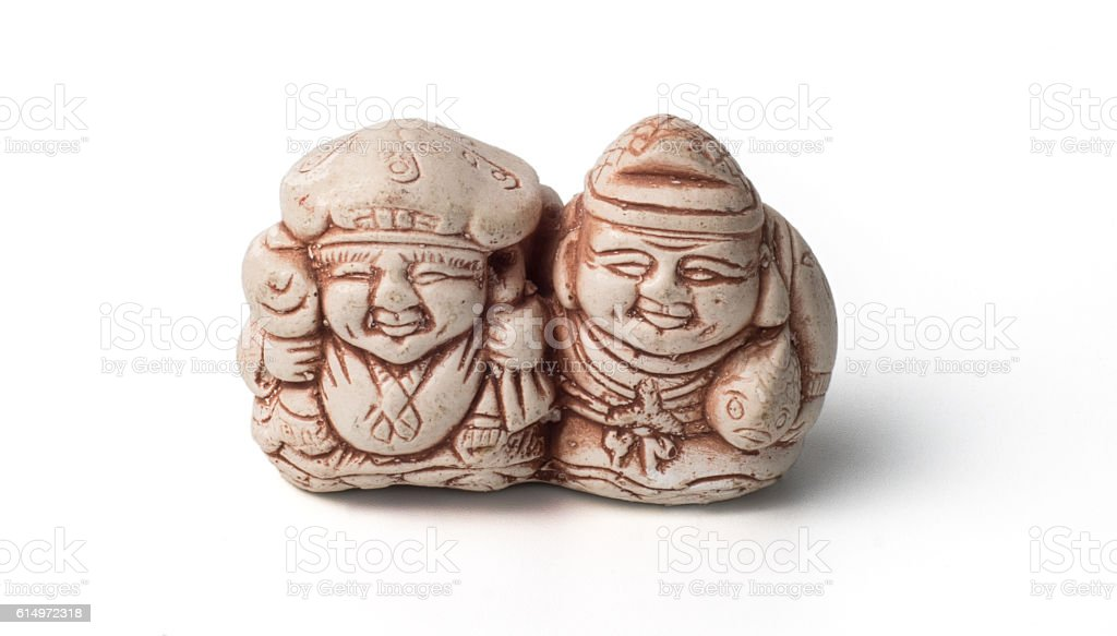 Netsuke of two fishermen with their catch. Isolated. stock photo