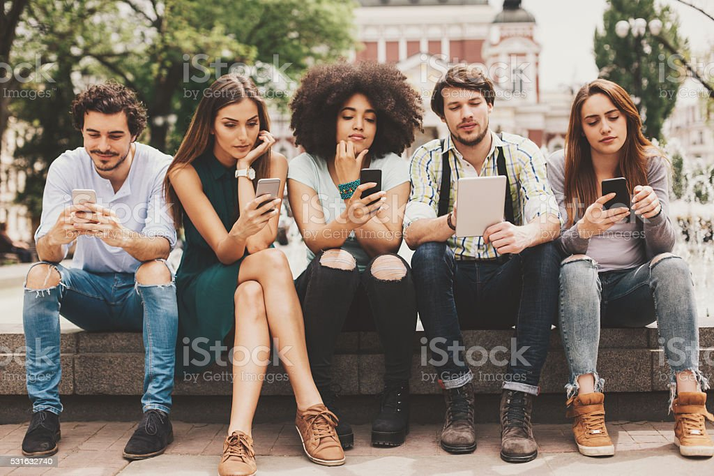 Group of mixed race people looking at mobile phones and tablets...