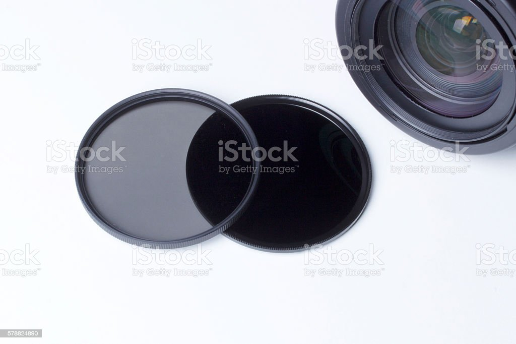 Neutral density photographic filters near a lens. stock photo