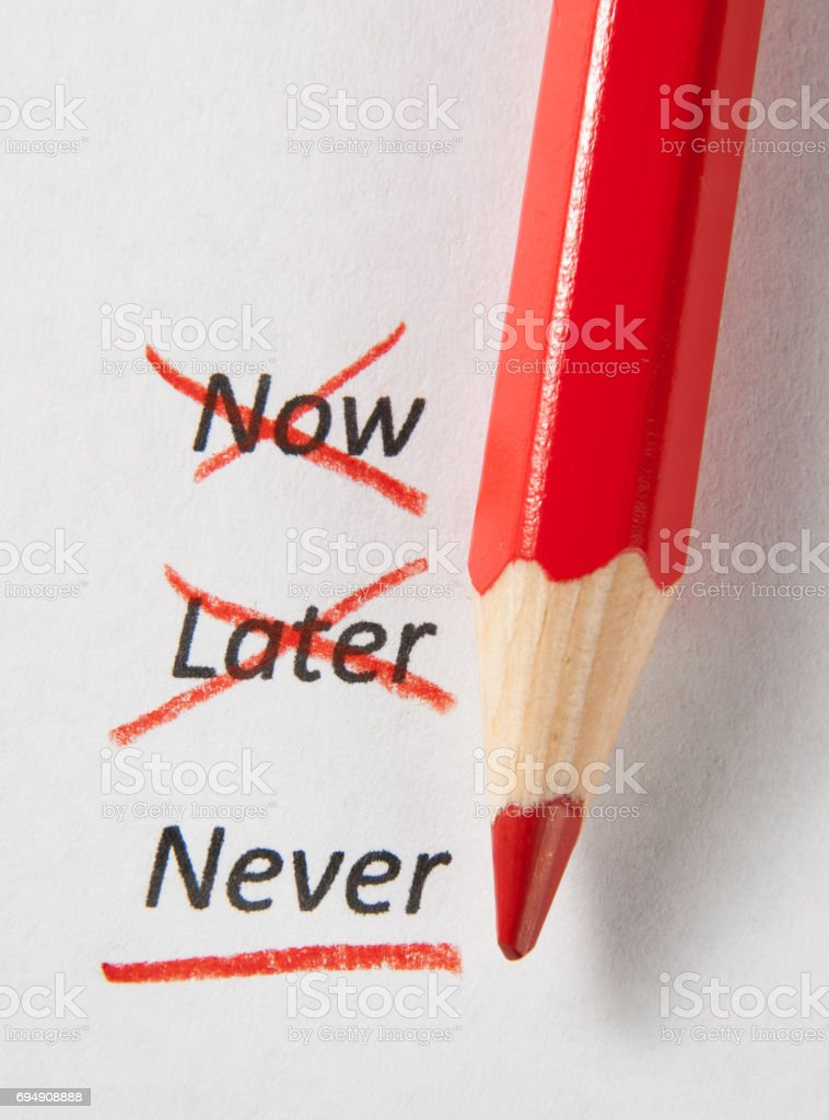 Never not now and later with red pencil stock photo