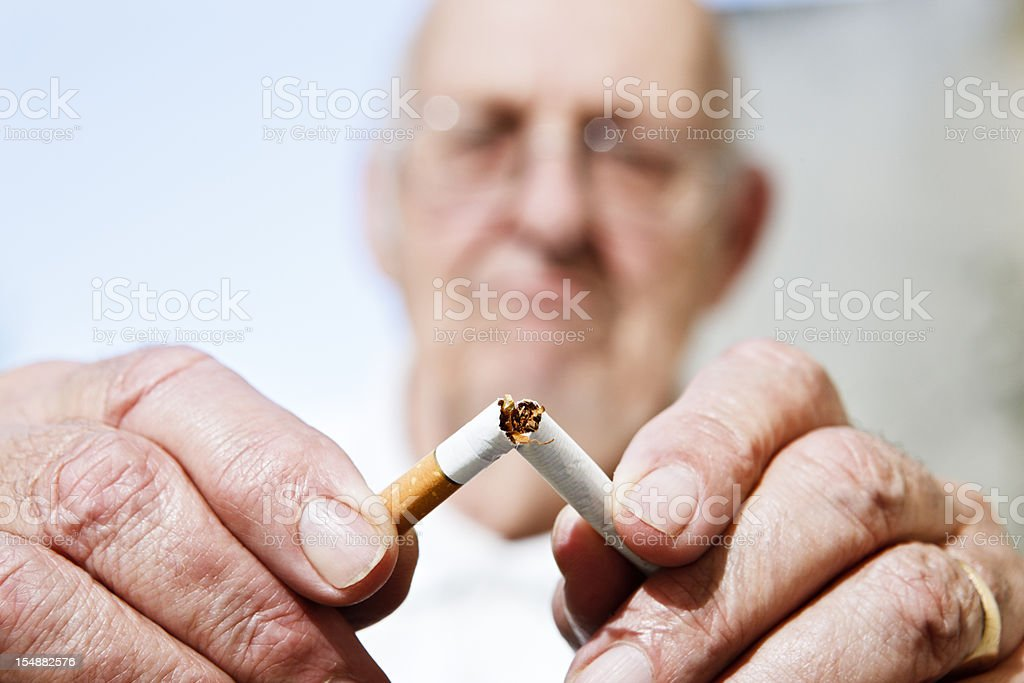 Never too late to stop smoking: old man breaks cigarette stock photo