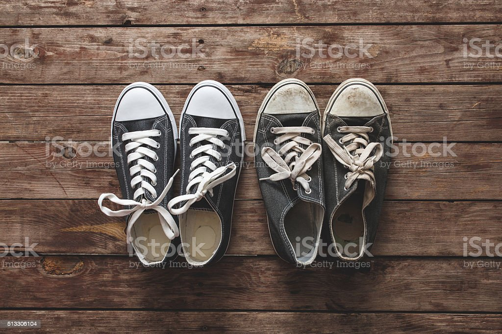 New and old sneakers on wooden background stock photo