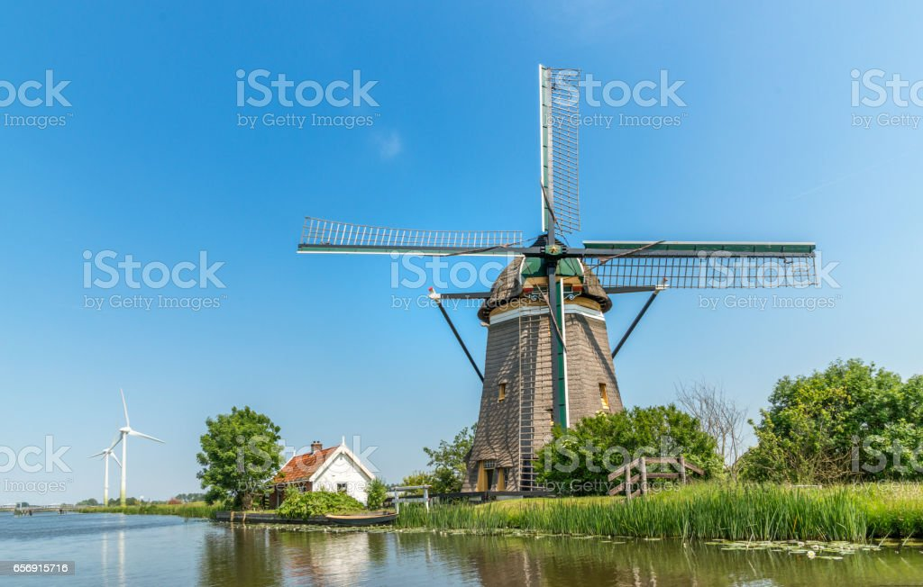 New and old windmills on waterfront in the Netherlands. stock photo