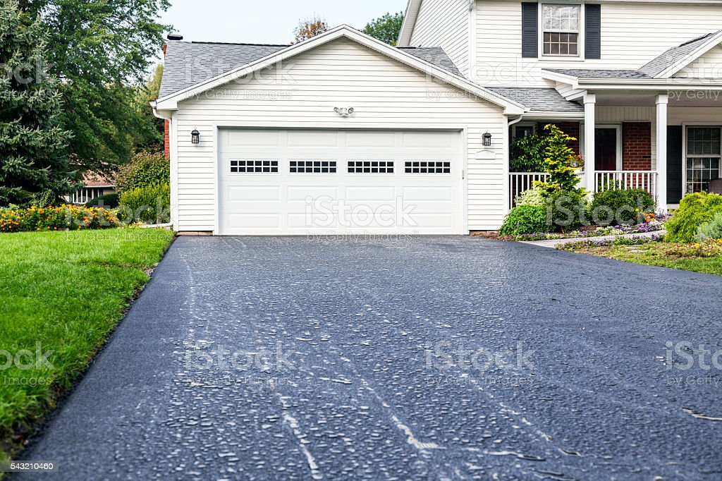 New Asphalt Driveway Rain Puddles at Residential Home stock photo