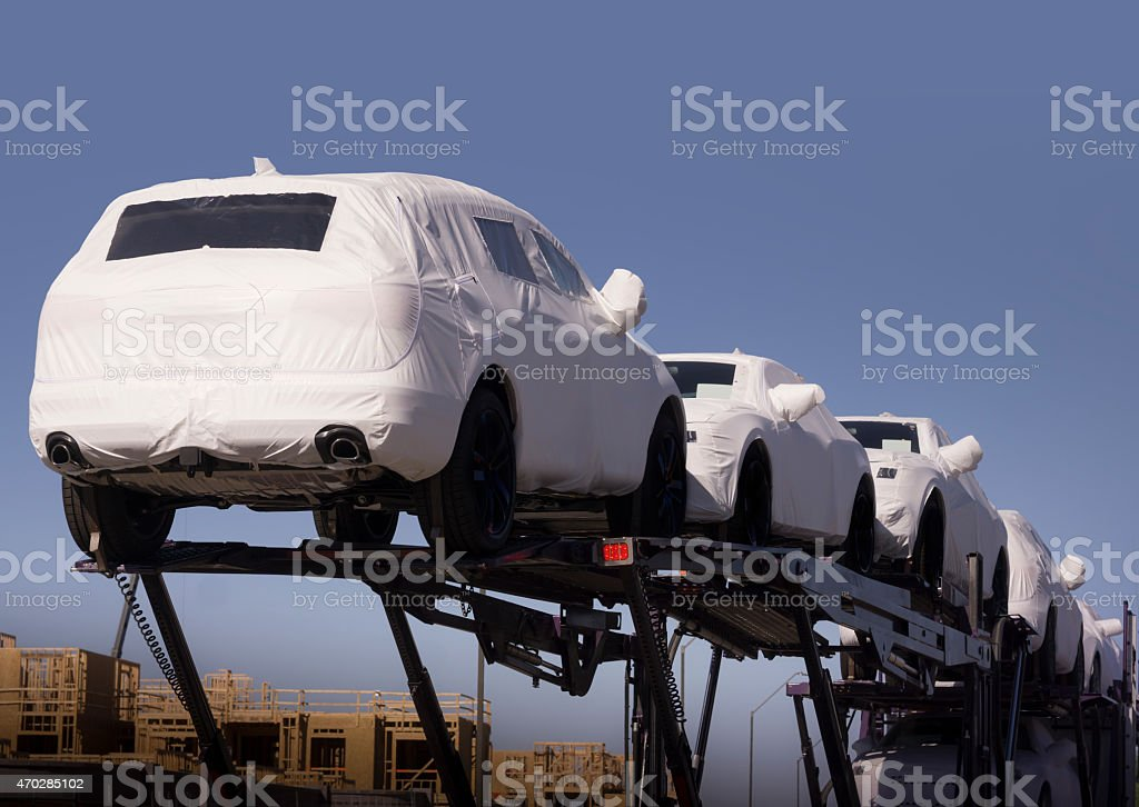 New auto cars under wraps being delivered on truck stock photo