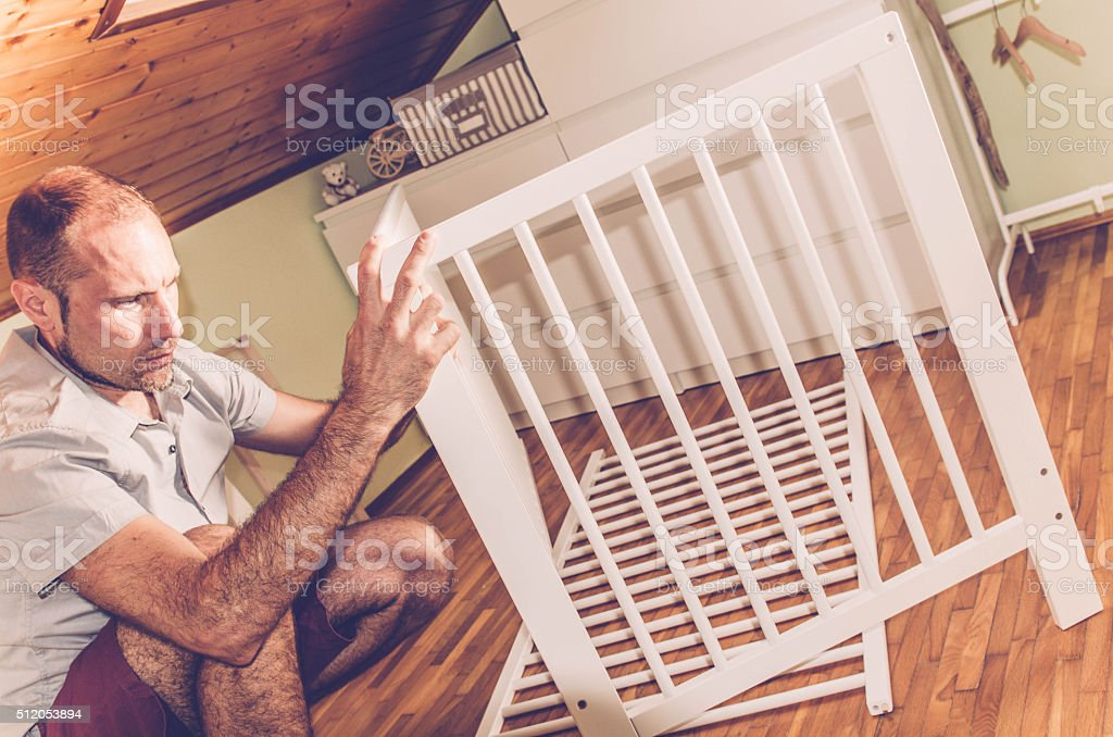 Man opening the baby cot furniture box; indoor photography.