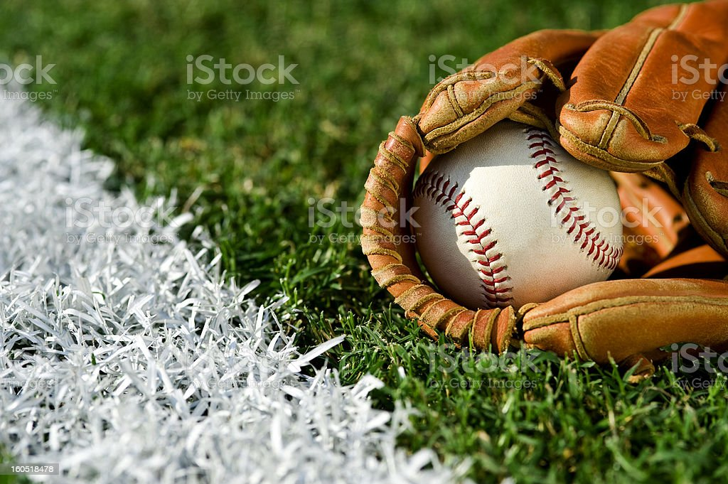 New Baseball in glove along foul line stock photo