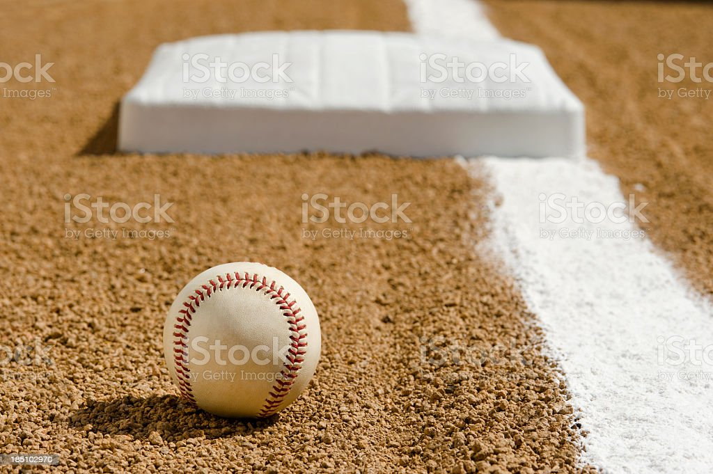 New Baseball on infield dirt by First base foul line stock photo