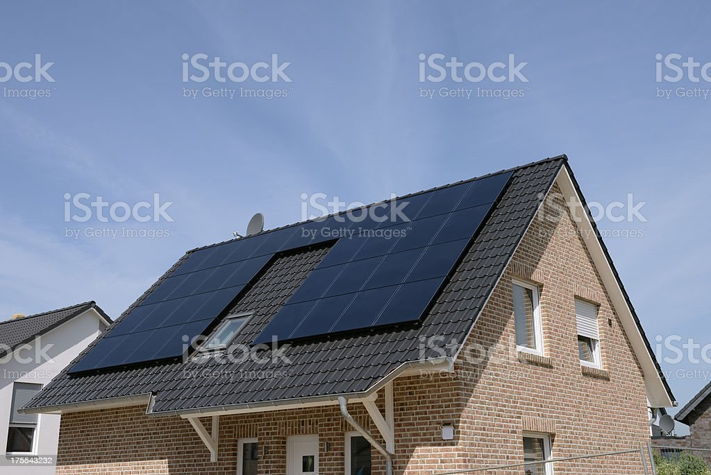New basic house with solar panels on the roof stock photo