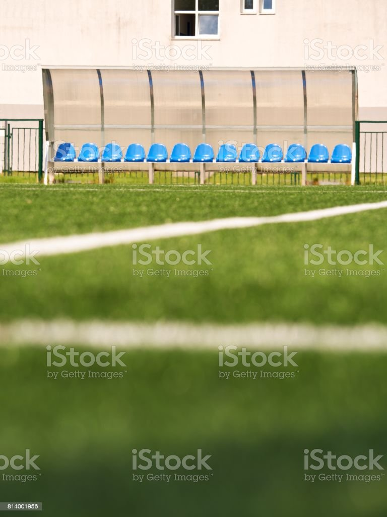 New blue plastic seats on outdoor stadium players bench, chairs under transparent plastic roof stock photo